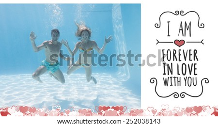 Cute couple smiling at camera underwater in the swimming pool against valentines message - stock photo