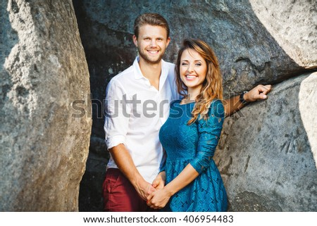 Cute couple standing together near rocks, outdoor. Girl wearing blue dress and man wearing white shirt and claret trousers, he has stylish haircut - stock photo