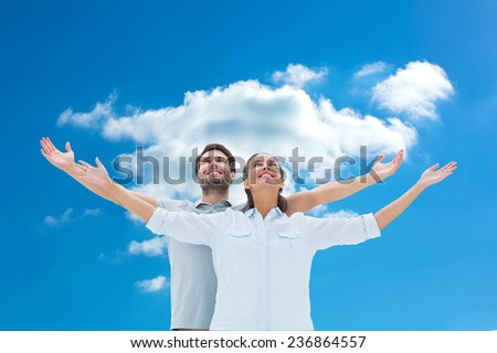 Cute couple standing with arms out against cloudy sky - stock photo