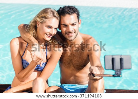 Cute couple taking selfie by the pool - stock photo