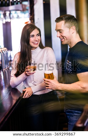 Cute couple talking and having a drink in a bar - stock photo