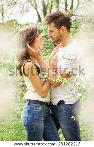 Cute couple touching each other in the blooming garden - stock photo