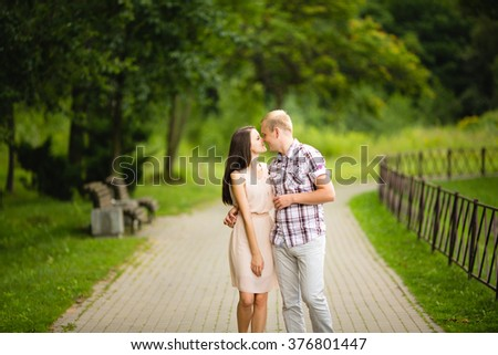 Cute couple walking hand in hand in a park - Romantic date outdoors - stock photo