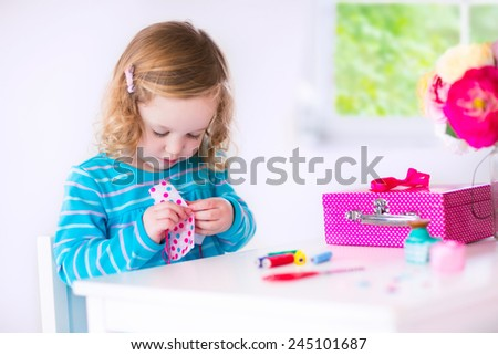 Cute creative little girl sewing a dress for her teddy bear doll, playing with needles and ribbons in a white sunny room at home or preschool - stock photo