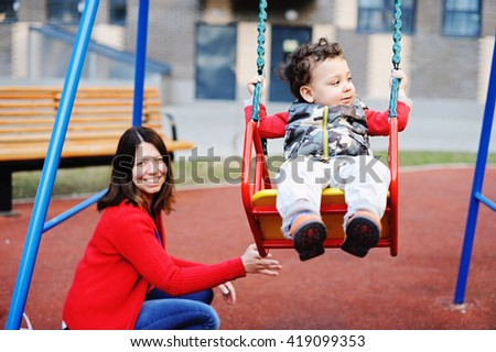 Cute curly baby boy having fun on a swing in the city  - stock photo