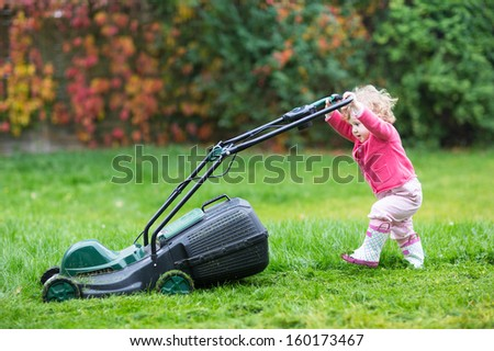 Cute curly baby girl in rain boots playing with a big green lawn mower in the garden - stock photo