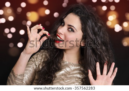 Cute curly hair young woman eating dark chocolate, bokeh beautiful background  - stock photo