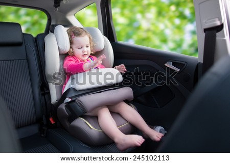 Cute curly laughing and talking toddler girl playing with a toy enjoying a family vacation car ride in a modern safe vehicle sitting in a baby seat with belt having fun watching out of the window  - stock photo