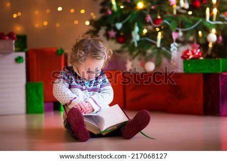 Cute curly little toddler girl in a warm knitted sweater sitting on a floor next to a Christmas tree reading a book enjoying cozy winter day at home - stock photo