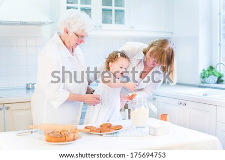 Cute curly toddler girl baking a pie with her grandmothers in a white beautiful kitchen - stock photo