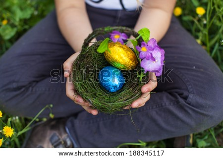Cute curly toddler girl  enjoying Easter egg hunt in the garden with blooming yellow forsythia flowers sitting on a white chair holding a basket with colorful eggs and a pink bow - stock photo