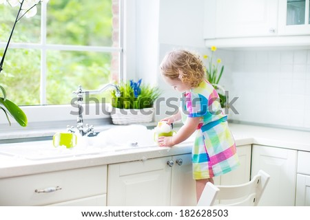 Cute curly toddler girl in a colorful dress washing dishes, cleaning with a sponge and playing with foam in the sink in a beautiful sunny white kitchen with a garden view window in a modern home  - stock photo