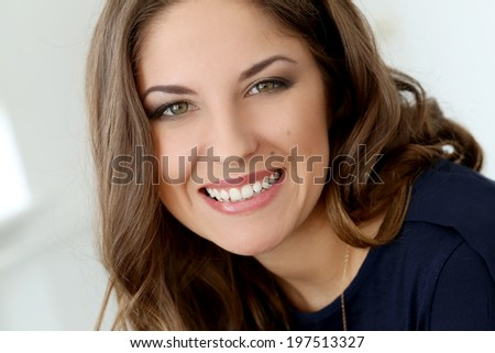 Cute, curly woman with wide smile - stock photo