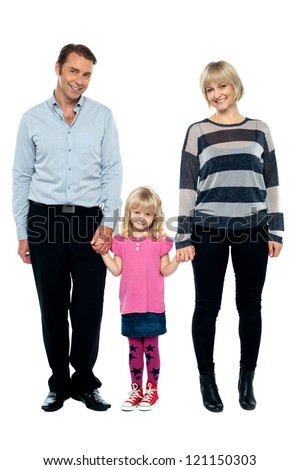 Cute daughter holding hands of her parents tightly. Full length studio shot. - stock photo