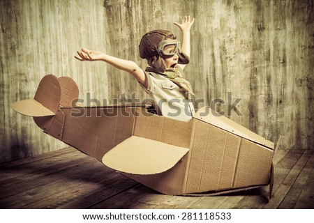 Cute dreamer boy playing with a cardboard airplane. Childhood. Fantasy, imagination. Retro style. - stock photo