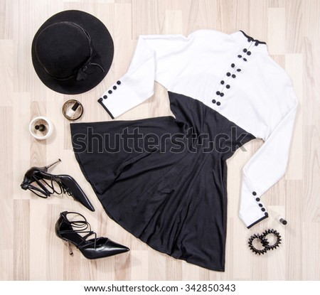 Cute dress with buttons and accessories arranged on the floor. Woman black and white dress with accessories, high heels, hat, bracelets lied down. - stock photo