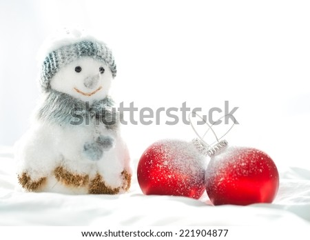 Cute dressed up snowman and Christmas balls in the snow. - stock photo