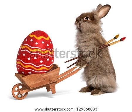 Cute Easter bunny rabbit with a little wheelbarrow and a red painted Easter egg, isolated on white, CG+photo - stock photo