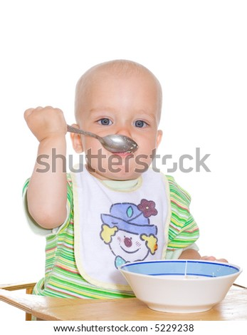 Cute eating child with spoon and plate. Isolated over white - stock photo