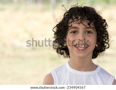 Cute eight years old Hispanic boy smiling with shallow depth of field in the countryside - stock photo