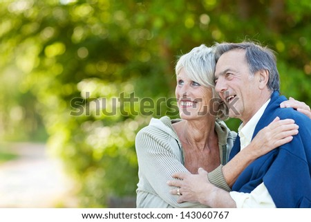 Cute elderly couple holding each other and laughing while looking at something. - stock photo