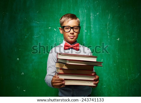 Cute elementary pupil in eyeglasses holding textbooks - stock photo