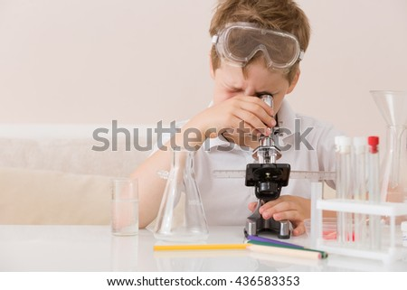 Cute elementary schoolboy looking into microscope at his desk at home. Young scientist making experiments in his home laboratory. Indoors. Child and science. Education concept. - stock photo