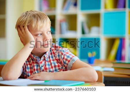 Cute elementary schoolboy sitting at lesson - stock photo