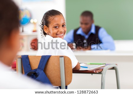 cute elementary schoolgirl in classroom with classmate and teacher - stock photo