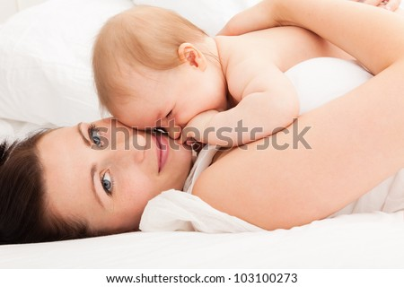cute embracing mother with baby in bed enjoying time together - stock photo