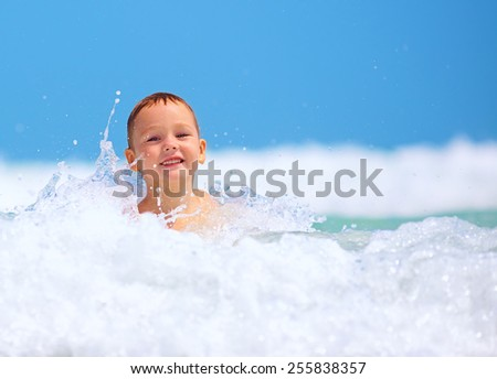 cute excited boy having fun in waves, summer vacation - stock photo
