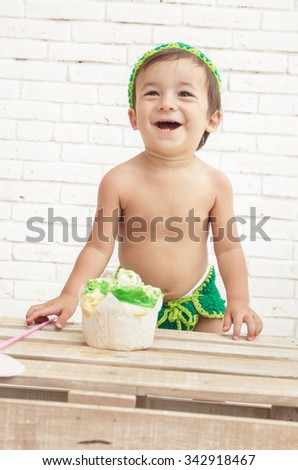 cute expression of adorable toddler wearing green hat with his sponge cake - stock photo