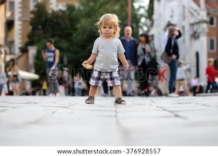 Cute fair-haired blond kid tiny little child baby boy with bun standing on flag-stone pavement in crowd cityscape on blurred grey background, horizontal picture - stock photo
