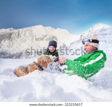 Cute family scene: father and son play with dog during mountain - stock photo