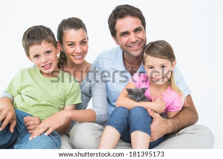 Cute family with pet kitten posing and smiling at camera together on white background - stock photo