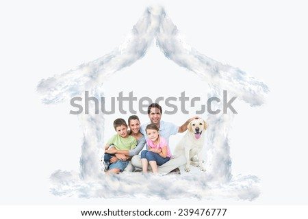 Cute family with pet labrador posing and smiling at camera together against house outline in clouds - stock photo