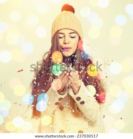Cute fashionable Caucasian brunette teenage girl blowing confetti. Pretty young woman with beige coat and knitted beanie hat. Square format, instagram filter, string light bokeh. - stock photo