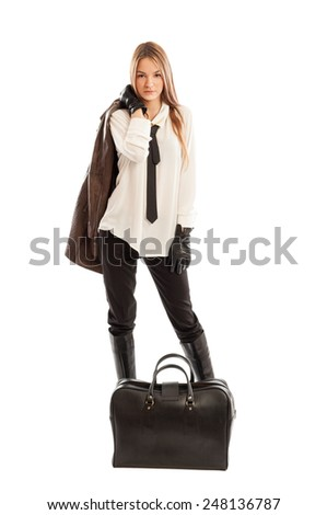 Cute fashionable female model holding brown leather jacket over the shoulder and black bag on the floor - stock photo