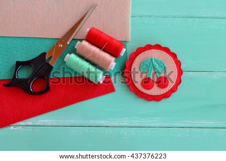 Cute felt brooch with red cherries and green leaves. Beautiful summer accessory for girls and women. Home made decoration brooch. Felt sheets thread kit, scissors, needle. Crafts supplies and tool  - stock photo