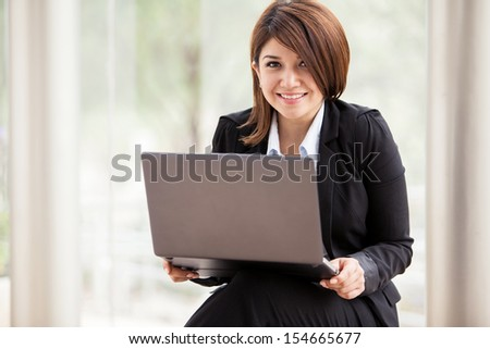 Cute female business school student doing some with a laptop computer and smiling - stock photo