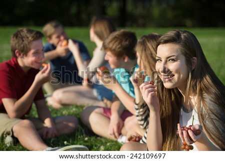 Cute female Caucasian teenager eating grapes with friends - stock photo