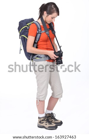 cute female hiker with camera isolated on white - stock photo