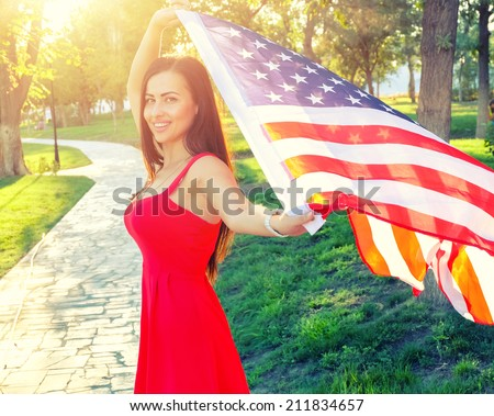Cute female in red dress with American nation flag in her hands. Happy young woman holding american flag. Baclit shot at sunset - stock photo