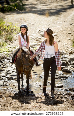 cute female kid jockey having fun learning riding pony outdoors happy with young Australian American horse instructor woman in cowboy look teaching the little rider in summer nature countryside - stock photo