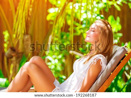 Cute female on tropical resort, sitting on deckchair with closed eyes and taking sun bath, enjoying exotic nature, summer vacation on Maldives  - stock photo