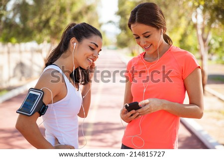 Cute female runners getting ready and sharing songs before going for a run - stock photo