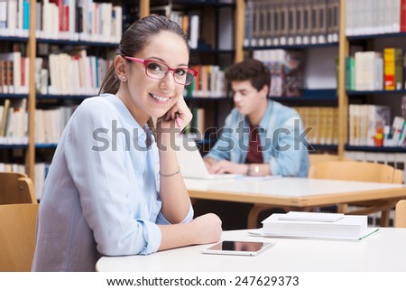 Cute female student with glasses studying at the library - stock photo