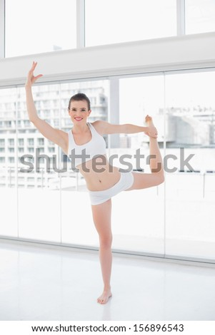 Cute fit brown haired model in sportswear doing fitness exercises in bright fitness studio - stock photo