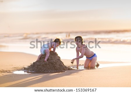 Cute funny baby girl climbing a sand castle her brother was building at a beautiful beach at sunset next to the water - stock photo