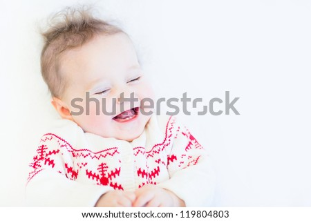 Cute funny baby girl laughing wearing a knitted snowflake sweater - stock photo